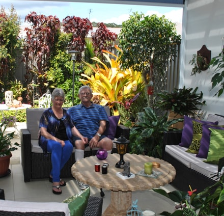 An elderly couple sitting down on a lounge in their retirement home backyard
