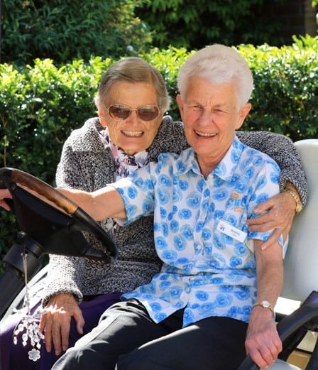 A female IRT carer in a golf cart with an eldery woman