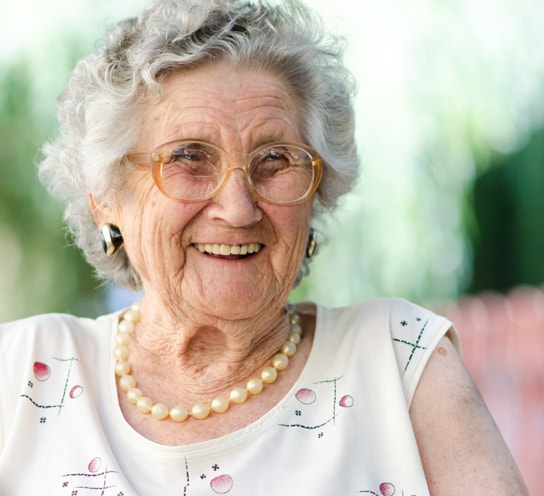 Elderly woman laughing with glasses on