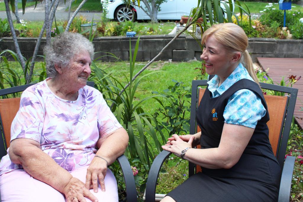 Carer sitting with elderly woman in retirement village backyard