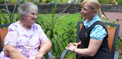 Carer sitting with elderly woman in retirement village backyard
