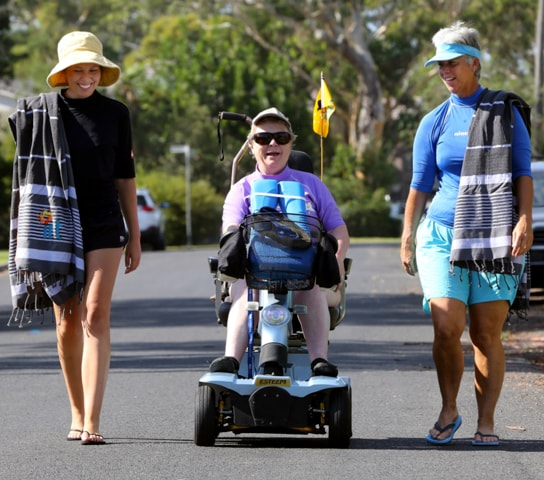 Two women walking with an eldery women in a mobility scooter