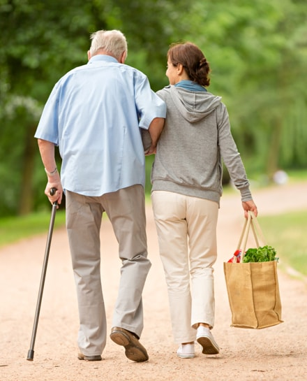 A younger woman holding an elderly mans arm while she carries his groceries