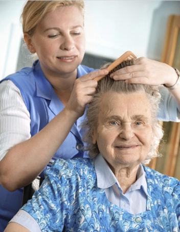 An IRT carer brushing an elderly woman's hair