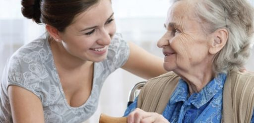 A women smiling at an elderly lady in a wheel chair