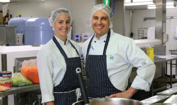 Two IRT Catering staff members wearing hair nets with aprons on