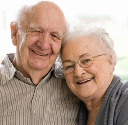 An elderly man and woman smiling