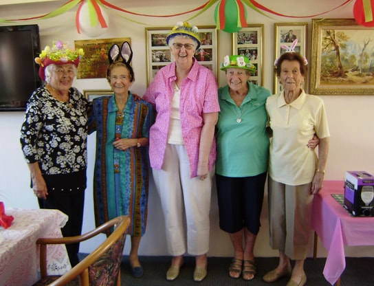 Five elderly women dressed in Easter hats in the retirement home