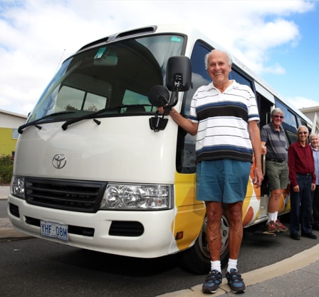 An elderly man standing next to retirement village bus