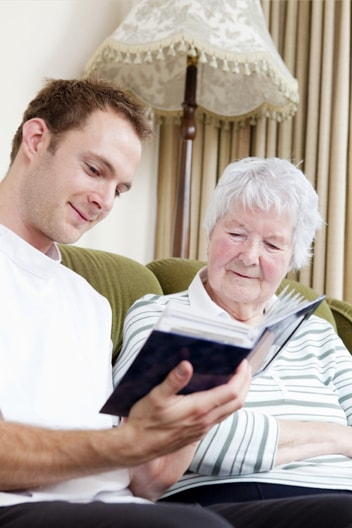 Young man and an elderly woman looking at a photo album together on the lounge