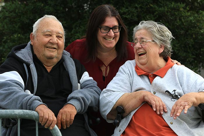 Two women and a man laughing together in an aged care retirement village