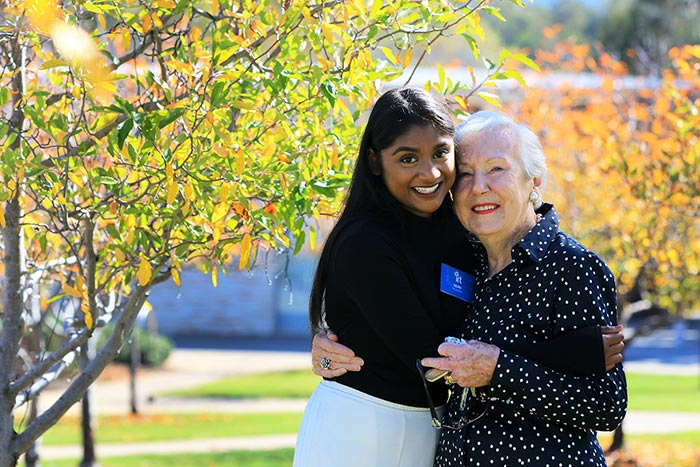 An IRT volunteer hugging an elderly female in a aged care facility garden