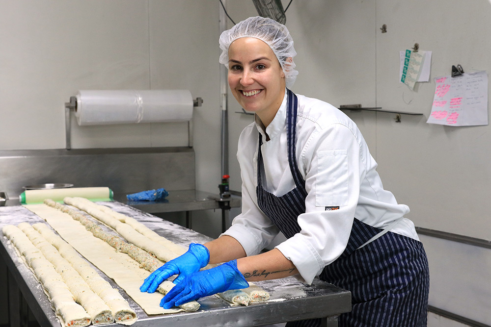 A chef rolling pastries in an industrial kitchen