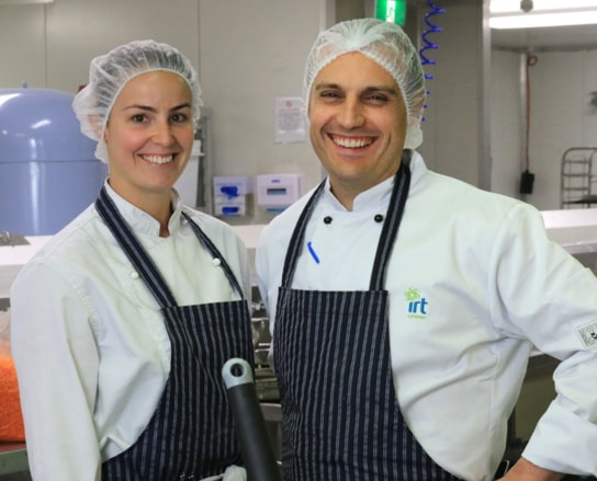 A man and a women wearing hair nets with aprons on, in the IRT kitchen