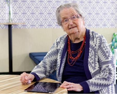 Elderly woman holding iPad in a retirement village