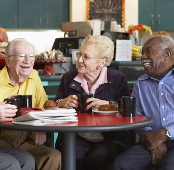 Two elderly males and an elderly woman enjoying morning tea together
