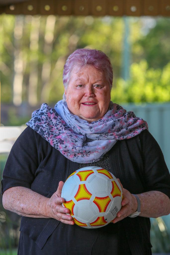 An elderly female holding a soccer ball in retirement village garden