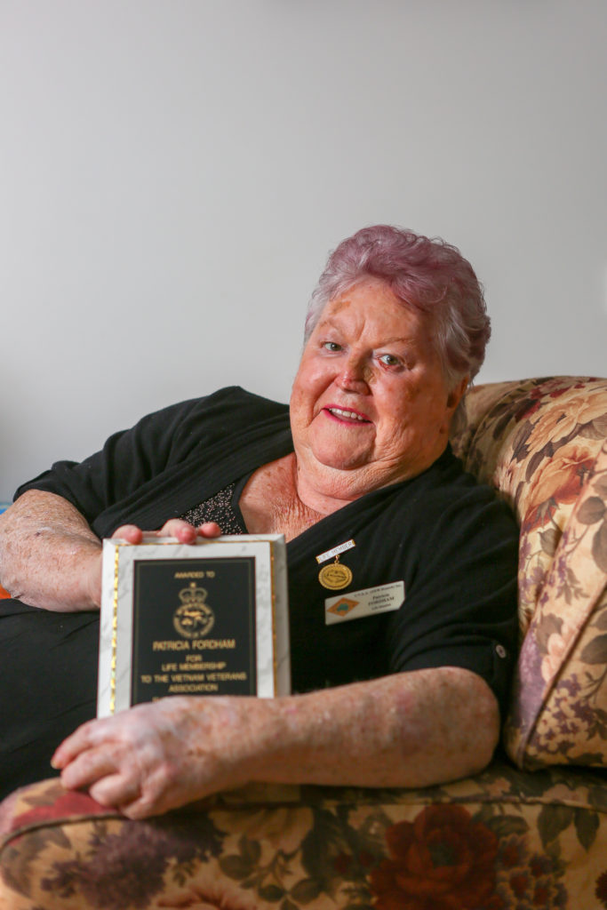 Elderly lady holding a certificate in a lounge chair