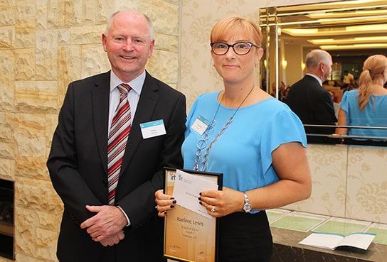 Two IRT staff members holding a certificate at IRT employee awards