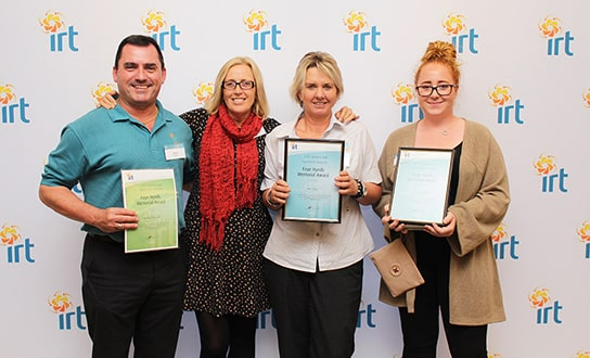 Four IRT staff members holding their certificates of achievement at IRT employee awards
