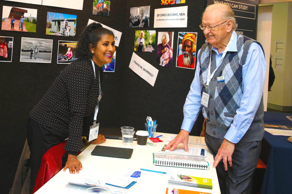 An elderly man talking with an IRT staff member at an expo