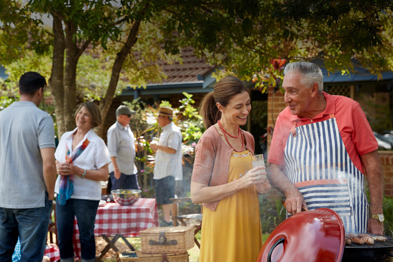 A group of men and women enjoying a BBQ in the retirement village backyard - Retirement Living Council Campaign