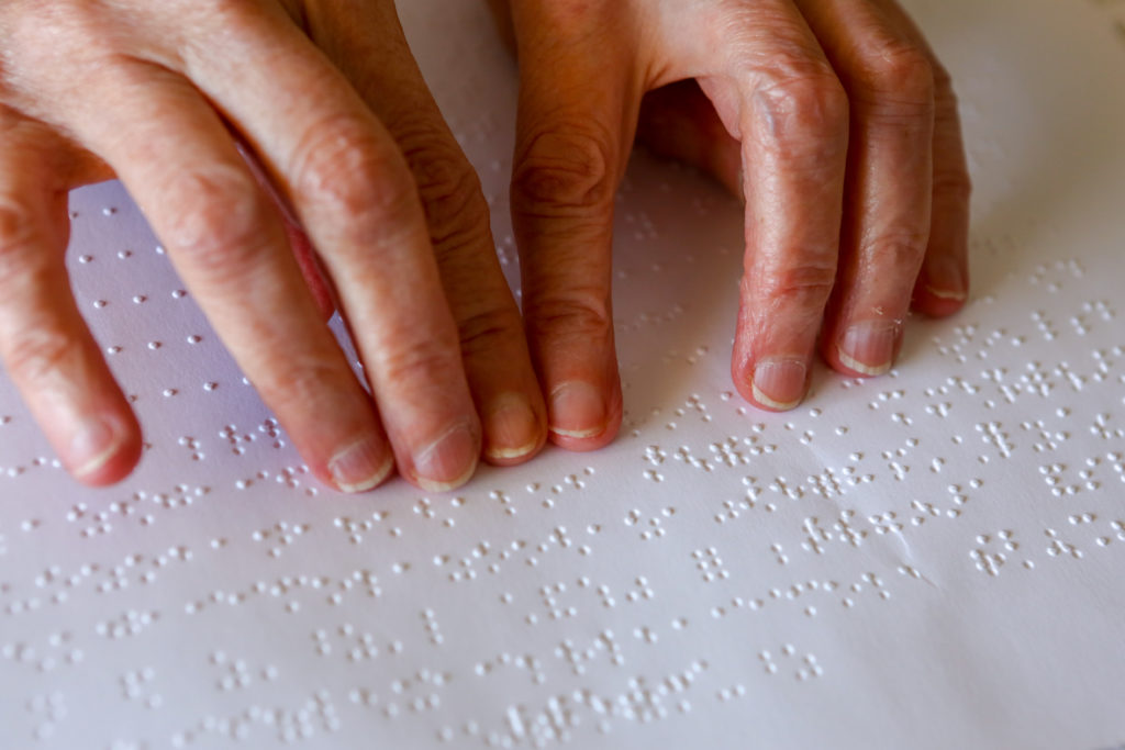 Two hands reading braille