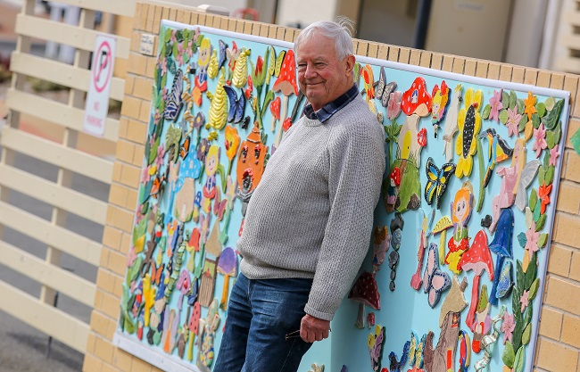 Our residents embrace creativity and an example is IRT Macarthur pottery teacher Michael Bright. He is standing in front of the community's pottery wall.