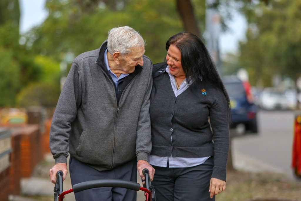 Home care worker with arm around older man