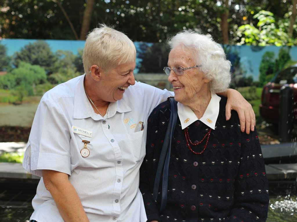 Aged care nurse laughing with elderly woman