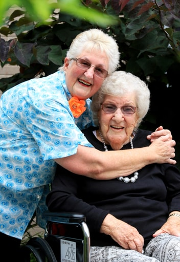 A woman hugging a another woman in a wheelchair