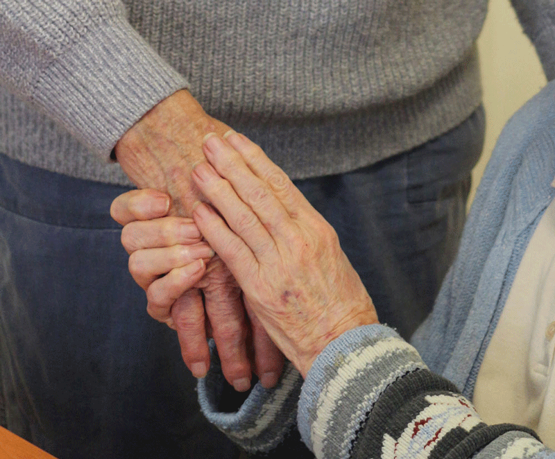 Supportive hands comforting an elderly person