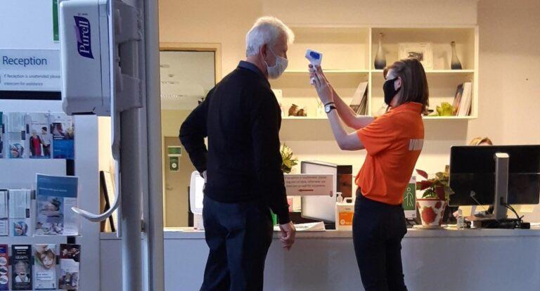 Wellness check volunteer takes visitors temperature