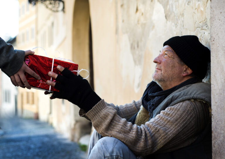 older homeless person receiving a gift