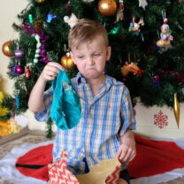 Young boy unwraps unwanted gift